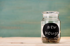 Mynt i exponeringsglas kan med det nya huset för tecknet på trätabellen Arkivbilder