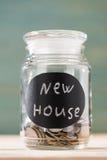 Mynt i exponeringsglas kan med det nya huset för tecknet på trätabellen Arkivbild