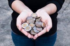 Mynt i händer som sparar, hus för marknad för utdelning för välgörenhet för donationinvesteringsfondekonomisk hjälp Royaltyfri Fotografi