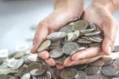 Mynt i h?nder Finans och investering coins sparande f?r stapel f?r begreppshandpengar skyddande arkivbilder