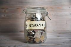 Mynt i krus med försäkringetiketten arkivbild