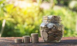 Mynt i krus med pengarbunten kliver växande pengar Royaltyfria Bilder