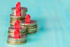 Mynt i rad med mini- hus Arkivfoton