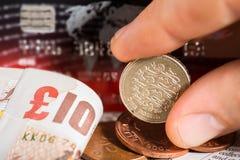 Mynt, kreditkortar och brittiska pund på tidningen Arkivbilder