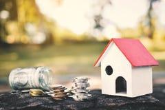 Mynt och det wood huset vaggar på bakgrundsbegrepp sparar pengar för hem Arkivfoto