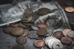 Mynt och dollarräkningar spridda på den konkreta tabellen royaltyfria bilder