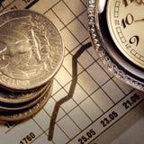 Mynt och klocka på diagram royaltyfri bild