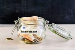 Mynt och pappers- pengar i en glass krus på trätabellen mot dar royaltyfria foton