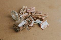 Mynt och räkningar som ut går från en tappad glass krus, över en trätabell Tappningfiltersignal royaltyfria bilder