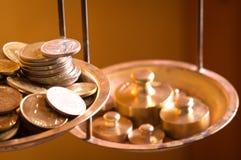 Mynt på en skalavikt Arkivfoto