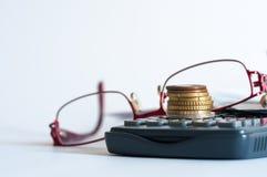 Mynt på räknemaskinen, monokel, blyertspenna arkivfoton