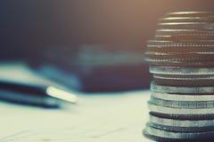 Mynt på skrivbordsarbete och räknemaskinen med pennbakgrund beträffande översikt Royaltyfri Foto