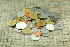 Mynt på wood bakgrund Arkivfoto
