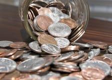 Mynt som dråsar från kruset Arkivfoto