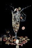 Mynt som faller in i ett champagneexponeringsglas royaltyfri bild