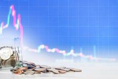 Mynt som spills från den glass kruset med att falla ner grafbakgrund förlora pengar, konkurs och fel i börsinvestering c Arkivbilder