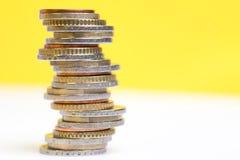 Mynt som staplas på de i olika positioner på vit bakgrund för en guling och arkivbild