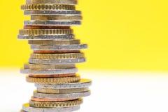 Mynt som staplas p? de i olika positioner p? vit bakgrund f?r en guling och arkivbilder