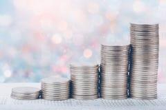 Mynt staplar framme av pengar för besparingar för bankkontoboken royaltyfri bild