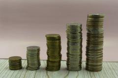 Mynt staplar framme av pengar för besparingar för bankkontoboken av myntbegreppet för egenskapsstege, intecknar och fastighetsinv fotografering för bildbyråer