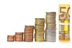 Mynta kolonner och rullande sedlar som isoleras över vit Royaltyfri Fotografi