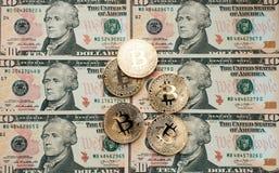 Myntar bitcoin, där är pengar, bordlägger på en anmärkning av 10 dollar Sedlarna är fördelade ut på tabellen i ett löst Royaltyfri Fotografi