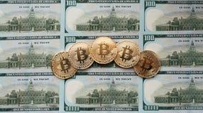 Myntar bitcoin, där är pengar, bordlägger på en anmärkning av 100 dollar Sedlarna är fördelade ut på tabellen i ett löst Fotografering för Bildbyråer