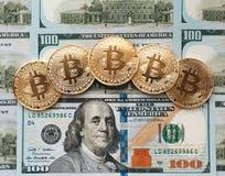 Myntar bitcoin, där är pengar, bordlägger på en anmärkning av 100 dollar Sedlarna är fördelade ut på tabellen i ett löst Royaltyfri Bild
