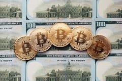 Myntar bitcoin, där är pengar, bordlägger på en anmärkning av 100 dollar Sedlarna är fördelade ut på tabellen i ett löst Royaltyfri Fotografi