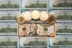 Myntar bitcoin, där är pengar, bordlägger på en räkning av 10 dollar Sedlarna är spridning på tabellen i en lös beställning av Royaltyfria Bilder