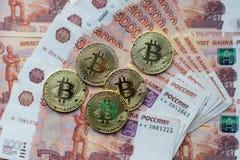 Myntar bitcoin, lögn på en räkning av 5000 tusen rubel Sedlarna är fördelade ut på tabellen i en fri beställning Royaltyfri Fotografi