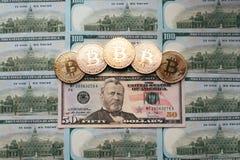 Myntar bitcoin, pengarlögnerna, på räkningtabellen av 50 dollar Sedlarna är spridning på tabellen i en fri beställning av 50 Royaltyfri Bild