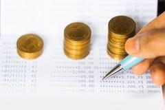 Myntar bunten och pennan på bankbankbokbakgrund royaltyfria bilder