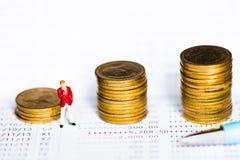 Myntar bunten och pennan på bankbankbokbakgrund arkivbild