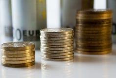 Myntar kolonner med bakgrund för pappers- pengar Arkivfoto
