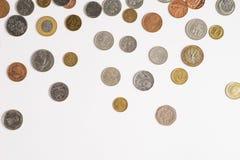 Myntar pengar p? en vit bakgrund arkivfoto