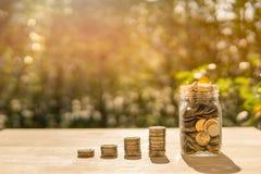 Myntar stången, och kruset på trätabellen i solljus- och suddighetsbakgrund framlägger besparingmynten royaltyfri foto