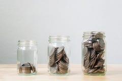 Myntet i krusmomentet som växer upp, begreppet sparar pengar eller investeringen fi Fotografering för Bildbyråer