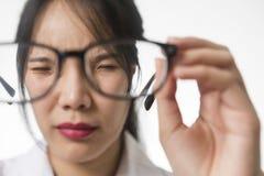 Myopi närbild av den unga kvinnan i glasögon royaltyfri foto