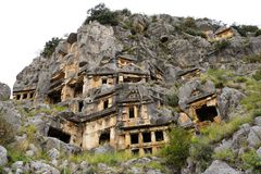 Myra rock tombs. There are two necropoli of Lycian rock-cut tombs in the form of temple fronts carved into the vertical faces of cliffs at Myra: the river Royalty Free Stock Image
