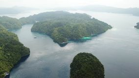 Aerial View of Islands and Channels in Raja Ampat. The myriad of beautiful tropical islands in Raja Ampat, Indonesia, are surrounded by coral reefs and calm seas stock video footage