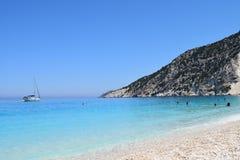 Myrthos海滩用小的白色蓝色石头和透明的水 免版税库存照片