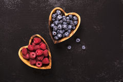 Myrtille et framboise dans des cuvettes en bois en forme de coeur Photos stock