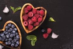 Myrtille et framboise dans des cuvettes en bois en forme de coeur Image libre de droits