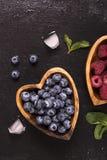 Myrtille et framboise dans des cuvettes en bois en forme de coeur Image stock