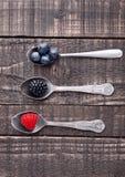 Myrtille et mûre de framboise sur la cuillère et la table en bois Photographie stock libre de droits