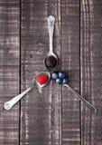 Myrtille et mûre de framboise sur la cuillère et la table en bois Image libre de droits