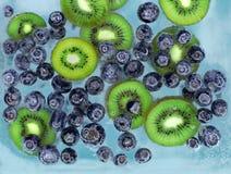 Myrtilles et kiwi descendant dans l'eau bleue avec des bulles d'air photo libre de droits