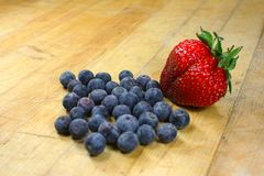 Myrtilles et une fraise o Photographie stock libre de droits