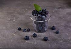 Myrtilles fraîches dans un seau transparent sur un béton gris photographie stock libre de droits
